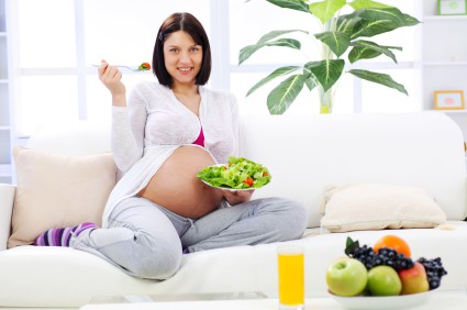Pretty pregnant woman eating vegetable salad.
